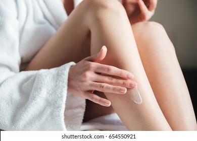 Closeup photo of young woman smearing cream on her leg