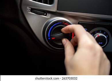 Closeup photo of young woman turning car air conditioner switch