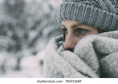 Closeup photo of a young woman wrapped in a long wool scarf, with winter hat, in nature