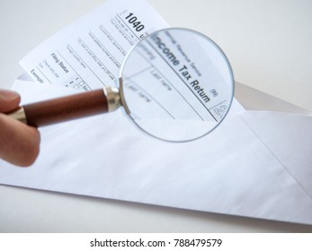 Closeup photograph of the 1040 federal government individual income tax return form in a white envelope with a man holding a magnifying glass over the text to enlarge it.