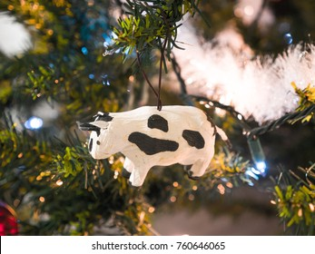 Closeup photograph of a beautiful handmade cow Christmas ornament hung from an artificial douglas fir green Christmas tree lit with lights making for a festive holiday background