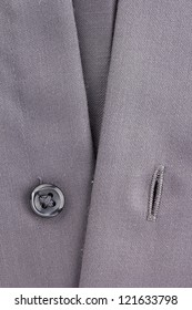 Close-up photograph of a black button on gray material.