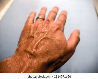 A closeup photograph of a Caucasian male hand with a sweaty hand extended outward with palm down with sweat drops beading on back of hand and raised veins with blue yoga mat beyond.