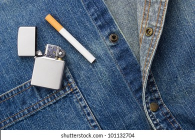 Close-up photograph of a cigarette and a silver lighter laying on denim material.