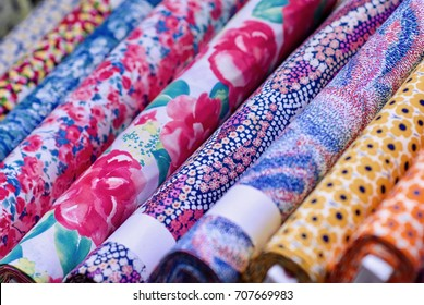 Close-up photograph of colorful bolts of cloth in a store.