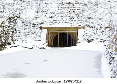 Closeup photograph of a drain pipe that provides storm water to a wet retention basin. The retention layer is covered by a thin layer of ice. A snow covers the ice and the retention basin's shore.