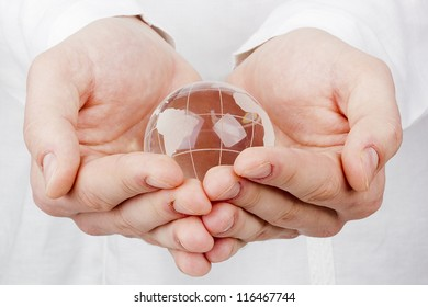 Close-up photograph of a glass globe in a man's hands.