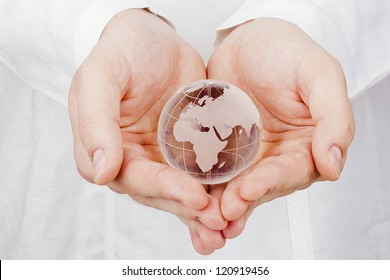 Close-up photograph of a glass globe in man's hands.