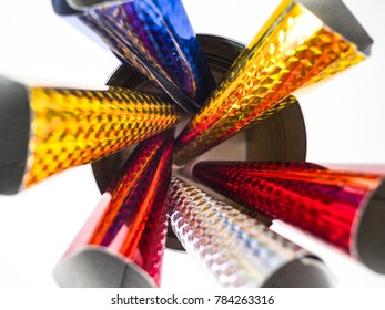 Closeup photograph looking down at several multi-colored holographic paper and plastic New Year's Eve celebration horns inside of a round can including red, yellow, blue, and silver.