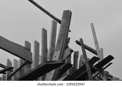 A close-up photograph of the planks - or ribs - of an unfinished wooden boat. The sky is grey. The photograph is in black and white.