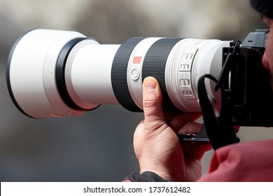 Closeup of a photographer holding onto a camera and large white telephoto lens while wearing a bright red jacket.
