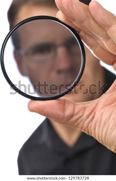 Closeup of photographer man holding and looking through circular polarizer filter