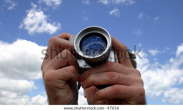 A closeup of a photographers hands taking a picture.