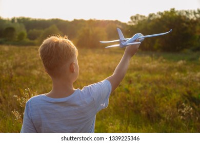 Closeup photography of back portrait of handsome young kid holding and enjoying his new toy blue plane. Boy standing in wild grass outdoors in sunset meadow on warm summer evening.