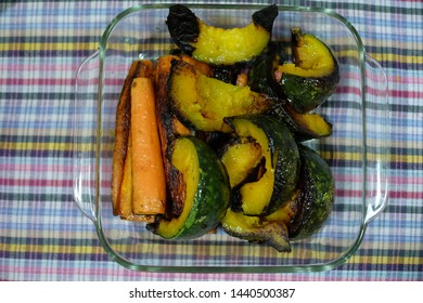 A close-up photography of grilled vegetables in a transparent and sqaure bowl on putting on a plaid tablecloth. Grilled Japanese pumkins and carrots.