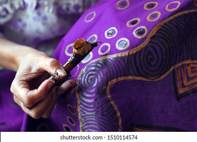 Close-up photos of a process of making purple written batik. Batik is a technique of wax-resist dyeing applied to whole cloth, or cloth made using this technique, originated from Indonesia