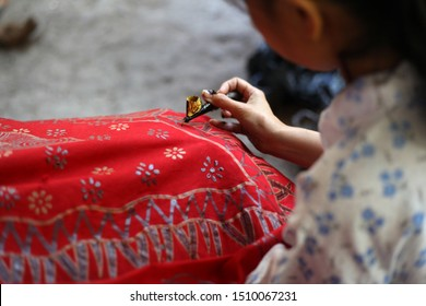 Close-up photos of a process of making written batik. Batik is a technique of wax-resist dyeing applied to whole cloth, or cloth made using this technique, originated from Indonesia