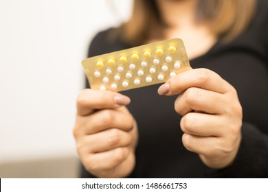 Close-up photos Young women hold birth control pills and condoms on hand. Concept of contraception methods