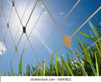 Closeup of a photovoltaic solar cell with sun glare and a fresh field of green grass