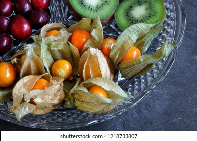 Close-up of Physalis fruit - Cape gooseberries with cranberries and kiwi on cut glass platter on slate background - with copy space