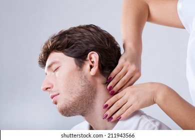 Closeup of physiotherapist palpationing patient with stiff neck