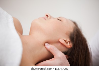 Close-up of physiotherapist pressing his thumb on the neck of a woman indoors