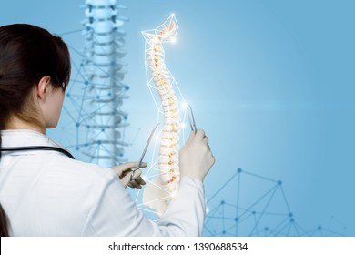 A closeup of a physiotherapist standing backside and operating with a spine model using constrictor and tweezers at the digital spine image background. A concept of spine diseases treatment.