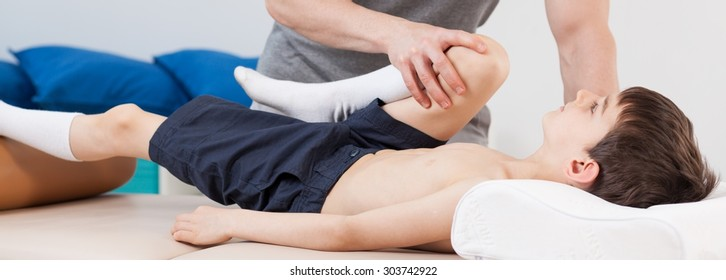 Close-up of physiotherapist stretching young patient's leg