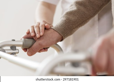 Close-up of physiotherapist supporting disabled senior man