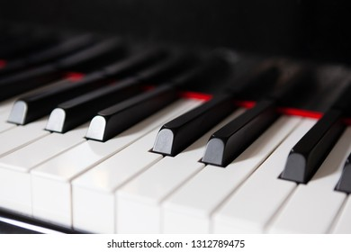 Closeup of piano keys with red stripe - music concept