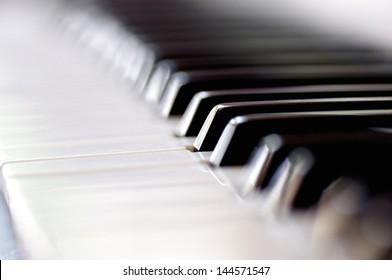 Nahaufnahme eines Pianos mit schwarz-weißem Schlüssel. Selektiver Fokus mit geringer Feldtiefe.