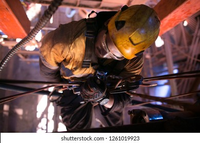 Closeup pic of male rope access abseiler miner maintenance fitter worker commencing abseiling rope body transferring in Y Hang positioning from right to left construction mine site, Perth, Australia