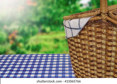 Closeup Of Picnic Basket On The Table With Blue Checkered Tablecloth And Summer Garden In The Background