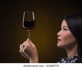 Close-up pictire of glass of expensive red wine. Professional sommelier woman studying new type of red wine. She is going to taste it.