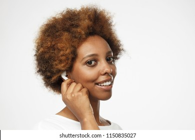 Closeup picture of beautiful dark-skinned lady isolated on grey background half-turned from camera, smiling, wearing white wireless earphones touching one of them to ensure better listening experience
