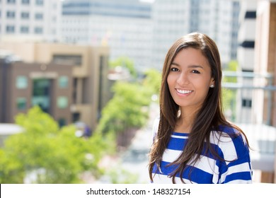 A close-up picture of a beautiful happy woman relaxing on a summer day on a balcony of a new apartment, on a city background