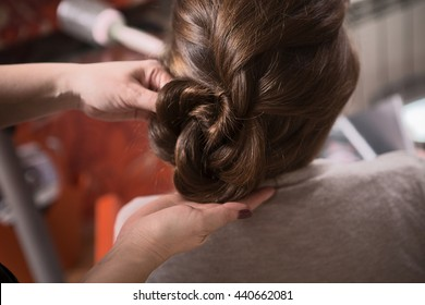 Closeup picture of beautiful lady sitting in chair and looking at mirror while hairdresser making braid in hairdressing saloon.
