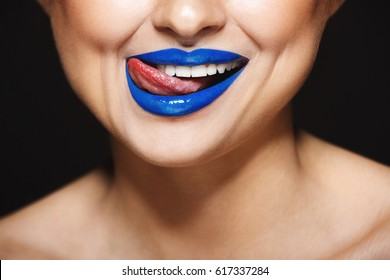 Closeup picture of cheerful girl's smile with blue lipstick. Tongue licking lips