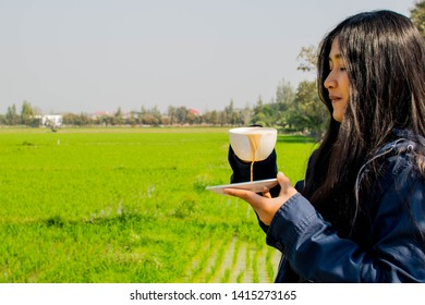 Closeup picture of clumsy Asian cute girl spilling coffee from a white ceramic cup and a saucer, outdoor on nature with a green grass field, on the horizon