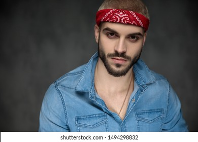 closeup picture of a cool young hipster wearing bandana and jeans shirt looking at the camera