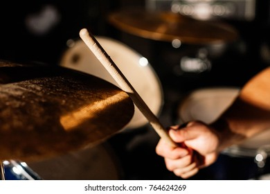 Close-up picture of a cymbal and a drumstick at the studio.