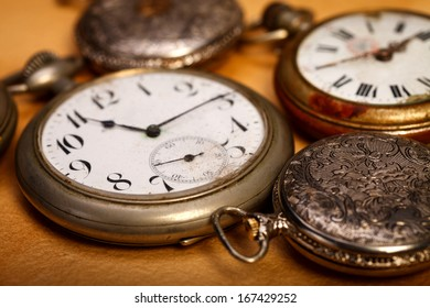 Closeup picture of different sizes pocket watches. Old paper background.