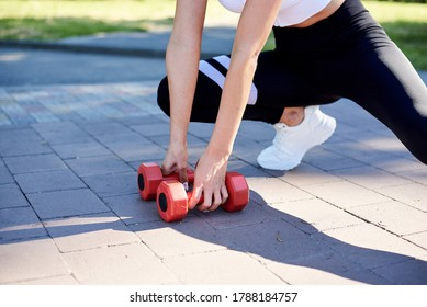 Close-up picture of female hands, holding red fitness weights, doing power morning exercises in city park in summer. Training process outdoors. Close-up image of woman's body, stretching.