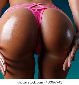closeup picture of female wet buttocks in pink panties over turquoise background