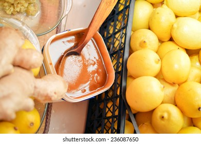 closeup picture of food making process wooden spoon in bowl & organic healthy ingredients as lemon, honey & ginger