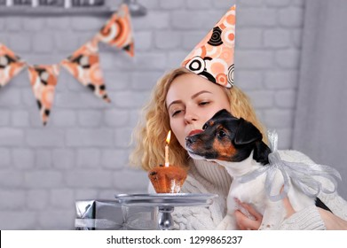 Closeup picture of a girl with dog blowing out the candle on the small birthday cake