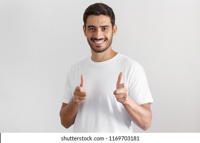 Closeup picture of good looking european man isolated on gray background, wearing white t-shirt, smiling happily and pointing to camera with both hands as if saying it is their turn