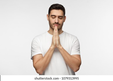 Closeup picture of handsome European man isolated on grey background in white casual T-shirt standing with closed eyes and hands pressed together as if meditating or praying, looking peaceful