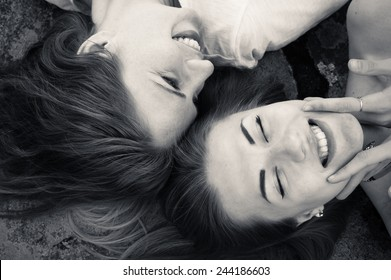closeup picture of happy girl friends relaxing head to head happy smiling