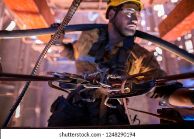 Closeup picture of industrial rope access miner fitter abseiling with static rope Hanging in Y hang position performing repairing connecting hydraulic hose system corner connecter at construction site